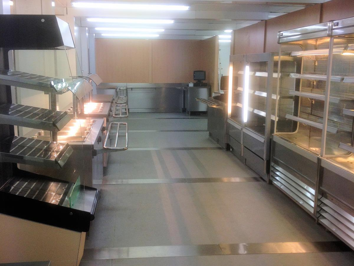 Self service area with refrigerated cabinets leading to a pay point and through to dining.